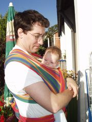 A father wearing his 4 month old infant in a sling